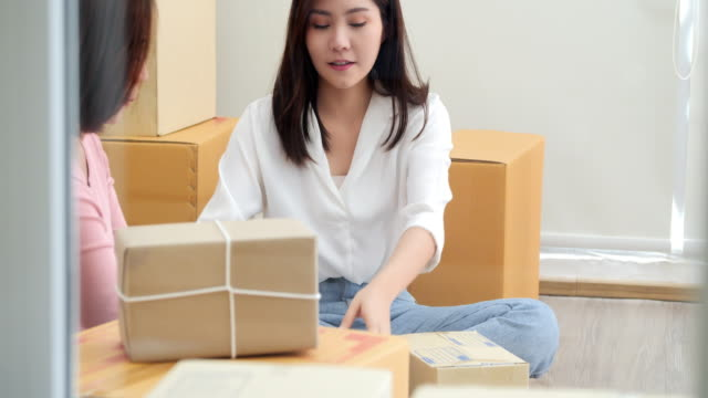 ホーム オフィス、オンライン マーケティングのパッケージ化と配信シーン、スタートアップ中小企業起業家やフリーランス女性自宅作業しているコンセプトで 2 人の若い女性の中小企業の� - 小荷物点の映像素材/bロール