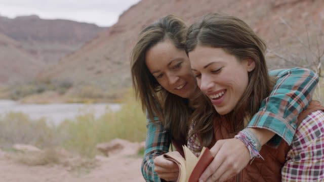 two young women smile at camera and flip through pages in travel journal at utah camp site. - diary stock videos & royalty-free footage