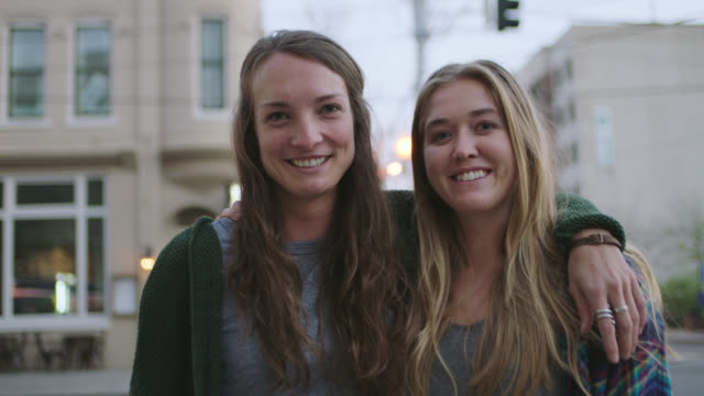 MS SLO MO. Two young women smile at camera on downtown city street corner outside local coffee shop.