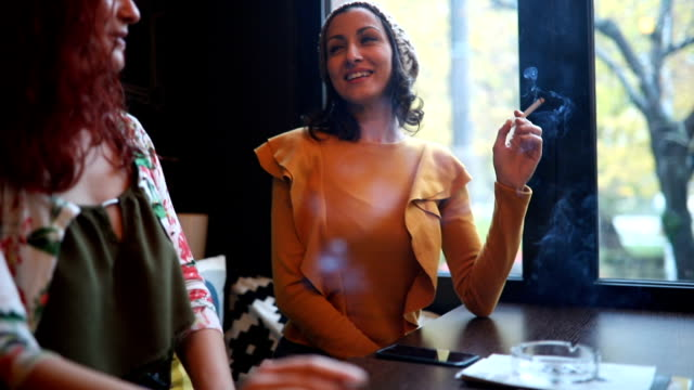 two young women smoking and having fun in the cafe - smoking issues stock videos & royalty-free footage