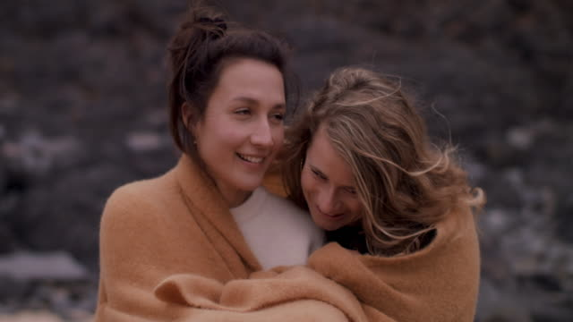 two young women snuggling under blanket, talking, sitting on beach - stringere tenere video stock e b–roll