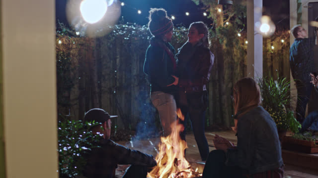 vidéos et rushes de two young women stand and embrace by fire pit at house party with friends. - loggia