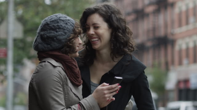CU Two young women standing on street, looking at mobile phone and laughing / New York City, New York, USA