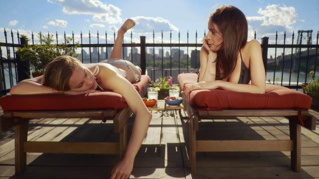 vidéos et rushes de ws two young women sunbathing on deck, one talking on cell phone / new york city, usa - bain de soleil