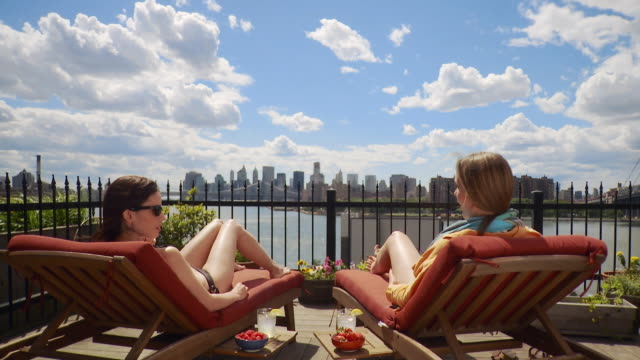 vidéos et rushes de ws td two young women sunbathing on deck overlooking east river and manhattan skyline / new york city, usa - bain de soleil