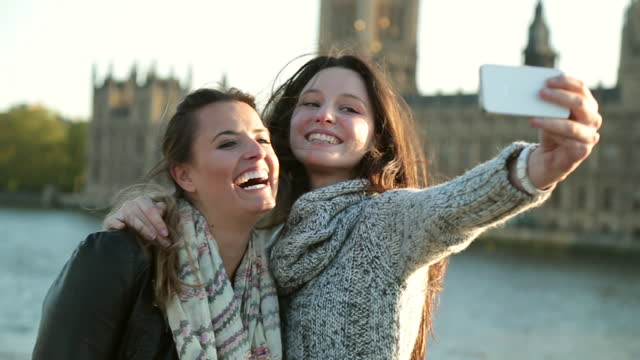two young women take a smartphone selfie in front of the palace of westminster in london. - 各国の観光地点の映像素材/bロール