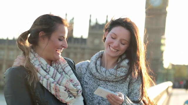 two young women take a smartphone selfie in front of the palace of westminster and elizabeth tower on westminster bridge in london. - tower bridge stock-videos und b-roll-filmmaterial