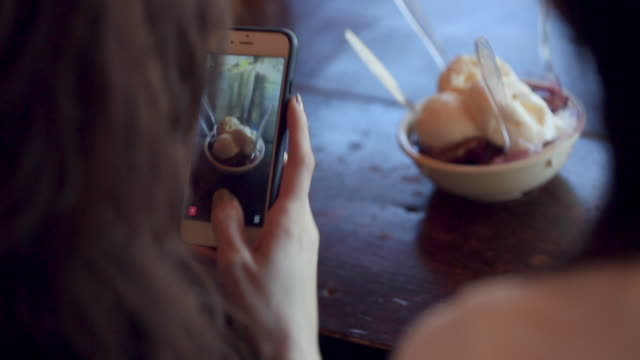 Two young women take photos of ice cream sundae with smartphone