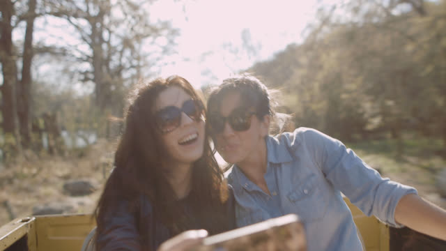 two young women take selfie and laugh in backseat of classic ford bronco - convertible stock videos and b-roll footage