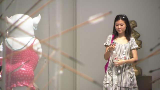 ms two young women taking photo inside art gallery, xin dong cheng space for contemporary art., beijing, beijing, china - 若い女性点の映像素材/bロール