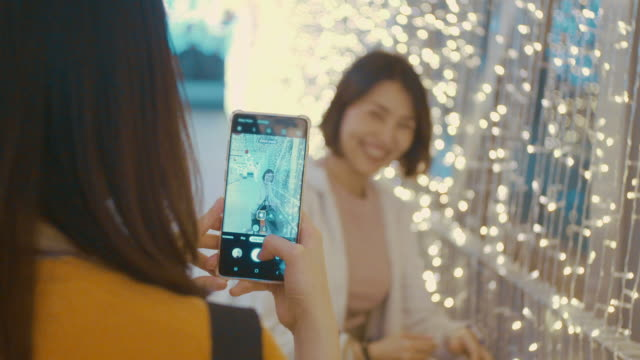 two young women taking photo with a mobile phone with lights decorated at christmas - photography stock videos & royalty-free footage