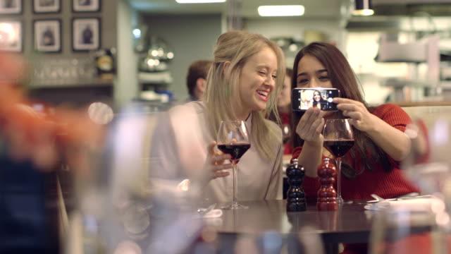 vídeos de stock e filmes b-roll de ms recipiente duas mulheres jovens tirar fotografias no restaurante - antena equipamento de telecomunicações