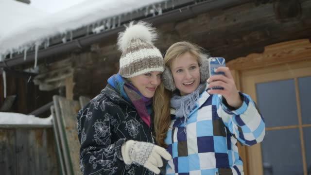 two young women taking selfie in snow - skijacke stock-videos und b-roll-filmmaterial