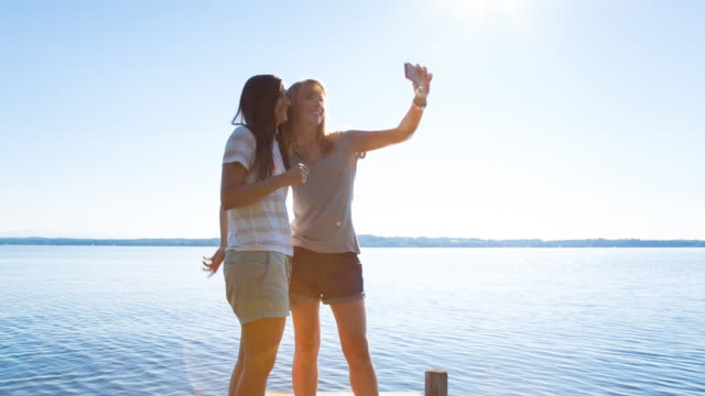 MS two young women taking selfie on lakeside deck