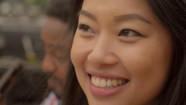 vidéos et rushes de two young women talk around the dinner table - multi ethnique
