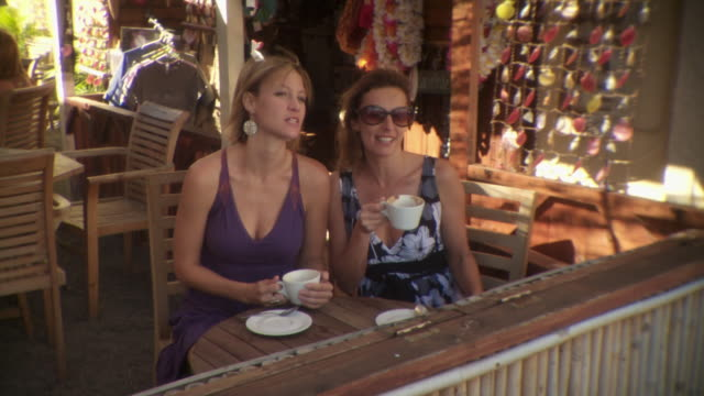 ms two young women talking and drinking coffee in outdoor cafe, maui, hawaii, usa - patio stock videos & royalty-free footage