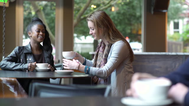 vídeos de stock, filmes e b-roll de two young women talking in a coffee shop - xícara de café