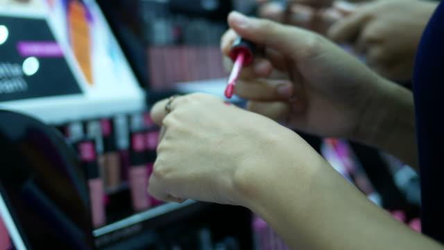 zwei junge Frauen testen Lippenstift im store