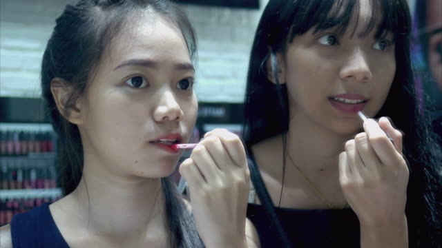 2 つの若い女性が店で口紅をテスト