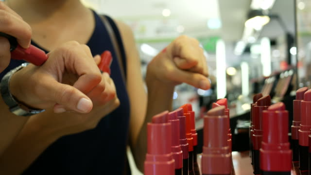 two young women testing lipstick at store - borsetta video stock e b–roll