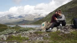 Two young women travelers using a smartphone with a view to a Norwegian fjord