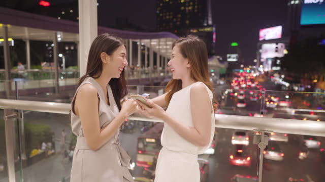two young women using smart phone at night - mar stock videos & royalty-free footage