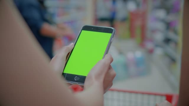 Two young women using smartphone in supermarket,Green screen