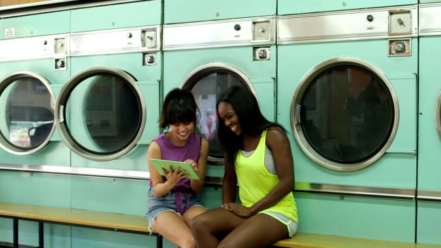 mls a two young women wait in a launderette - 輪っかのイヤリング点の映像素材/bロール