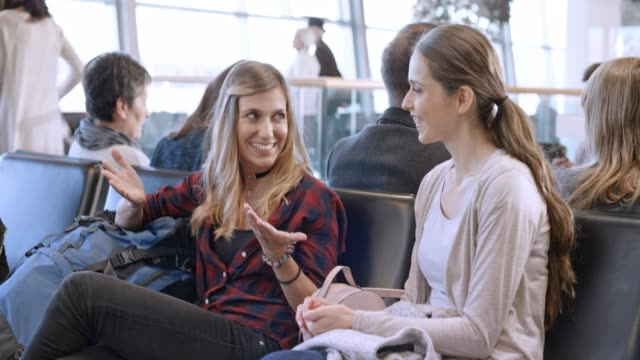 two young women waiting for boarding at the airport and talking in the meantime - ethnicity stock videos & royalty-free footage