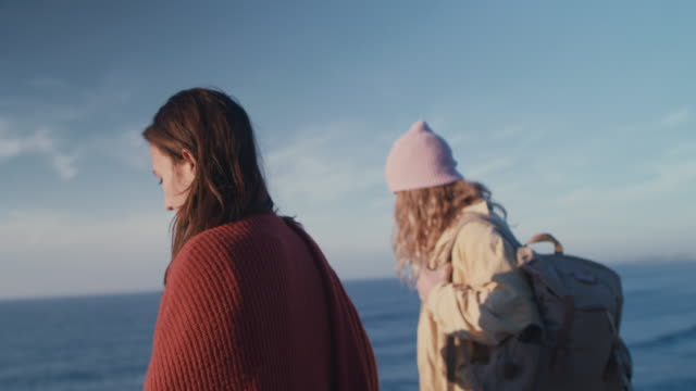 two young women walking along sea cliffs - hüten stock-videos und b-roll-filmmaterial