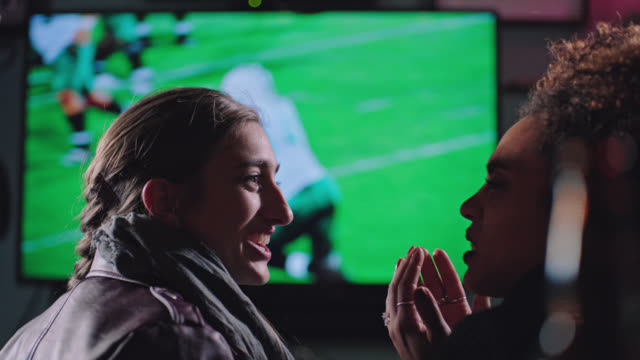 two young women watching football in local sports bar cheer at big interception. - bisexuality stock videos and b-roll footage