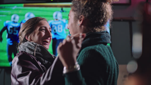 two young women watching football in local sports bar jump and down and embrace after touchdown. - american football sport stock videos & royalty-free footage