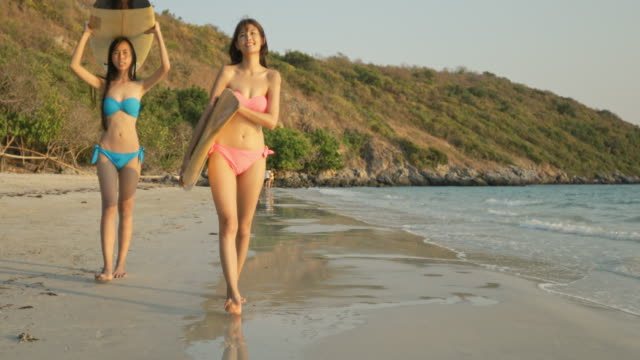 vídeos de stock e filmes b-roll de two young women wearing bikinis bright colors lift surfboard walking on the beach with the sea with bright sunny morning. - roupa de natação