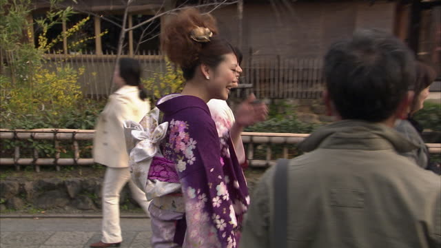 cu pan ms two young women wearing kimonos on street, gion, kyoto, japan - motivo floreale video stock e b–roll