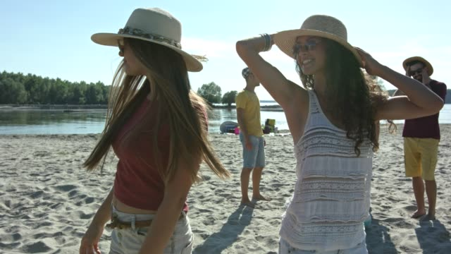 Two young women with hat enjoying time on river beach.