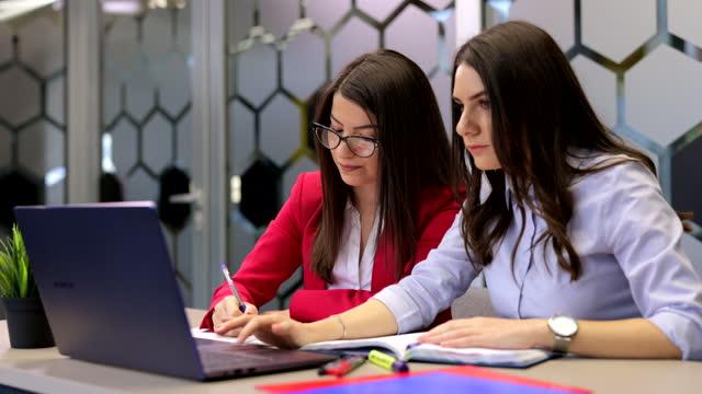 två unga kvinnor som arbetar på kontoret - employee engagement bildbanksvideor och videomaterial från bakom kulisserna