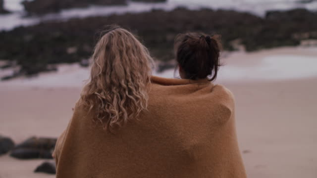 two young women wrapped in blanket sitting, looking at ocean - friendship stock videos & royalty-free footage