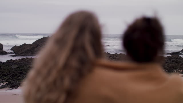 two young women wrapped in blanket sitting, looking at ocean - blanket stock videos & royalty-free footage