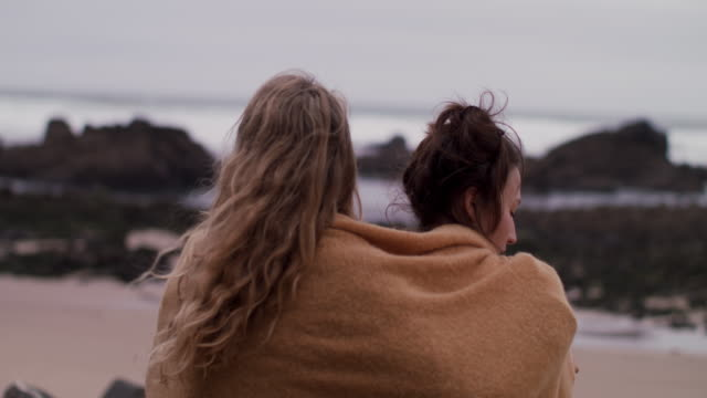 Two young women wrapped in blanket standing, looking at ocean