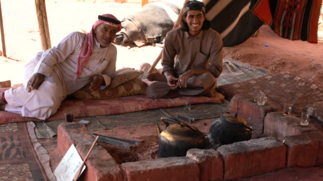 two zalabia bedouins drinking tea in a camp in wadi rum desert, jordan - ベドウィン族点の映像素材/bロール