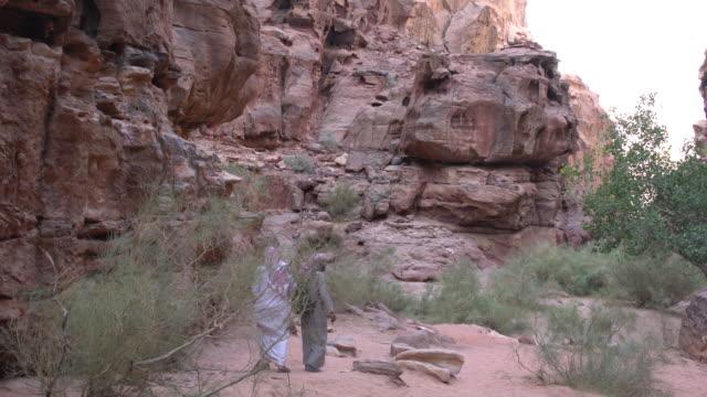 Two Zalabia Bedouins wearing traditional Arabic clothing walking alongside huge rocks  in Wadi Rum Desert, Jordan