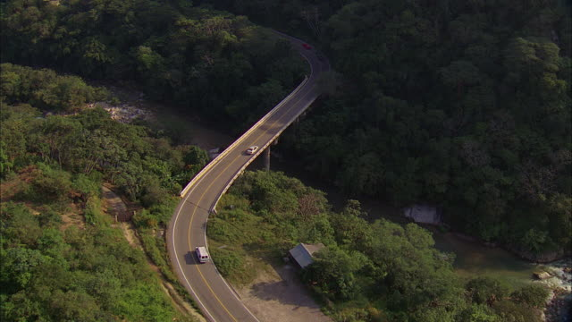 aerial two-lane highway and bridge over river in forested area with steep slopes - formato panoramico con bande nere video stock e b–roll