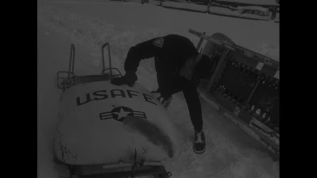 twoman sled whizzes past / people gathered around empty sleds at start of race course / vs usafe sled maneuvered into place men examine upended sled... - bobsleighing stock videos & royalty-free footage