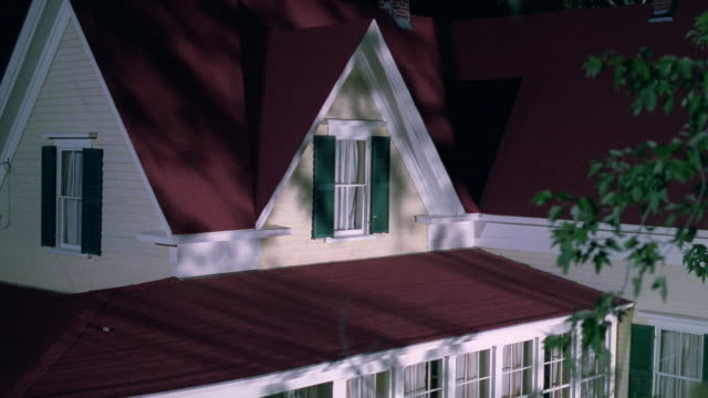 a two-story home features a red roof. - zweistöckiges wohnhaus stock-videos und b-roll-filmmaterial