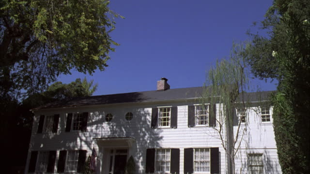 td two-story white clapboard house with black shutters - kolonialstil stock-videos und b-roll-filmmaterial