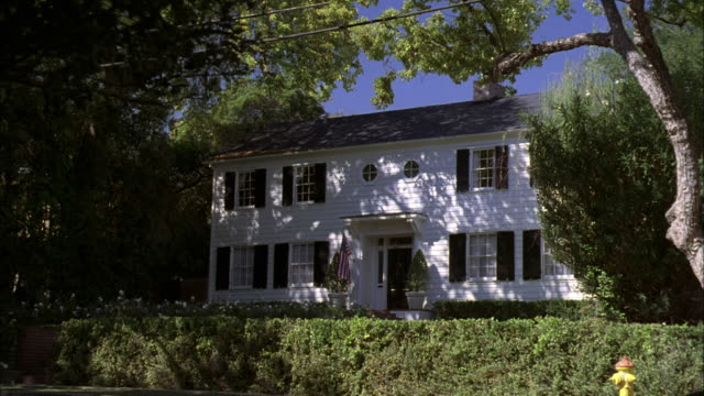 LA Two-story white clapboard house with black shutters
