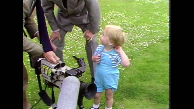 two-year-old prince william is shown a video camera by an itn camera person and looks through the viewfinder as his parents watch and the press takes... - toddler stock videos & royalty-free footage
