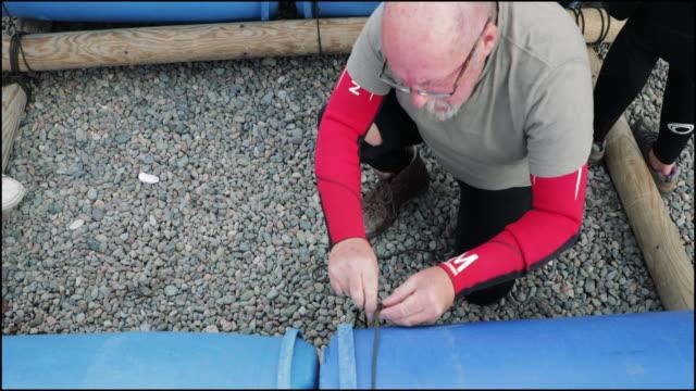 vídeos de stock, filmes e b-roll de amarrando barris juntos na atividade de construção de equipe - diving suit