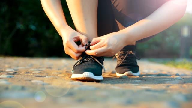 vídeos de stock, filmes e b-roll de amarrando os sapatos desportivos para correr - tênis calçados esportivos