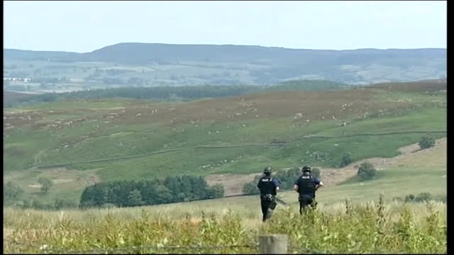 day six of manhunt for raoul moat / two men appear in court back view of armed police officers along past sheep armed officers in fieldon hillside - 登場点の映像素材/bロール